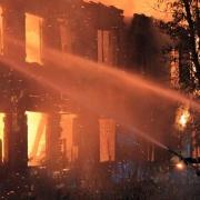 Incendio de un edificio con bombero tratando de apagar el fuego