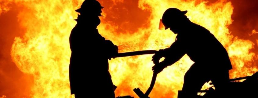 La figura de dos bombero con una muralla de fuego detrás de ellos